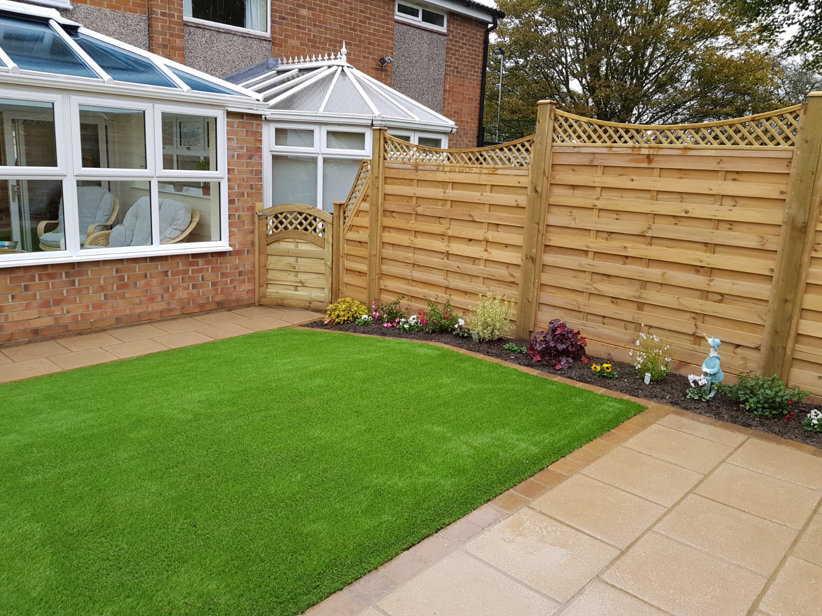 paved path with artificial grass and decorative fence panels
