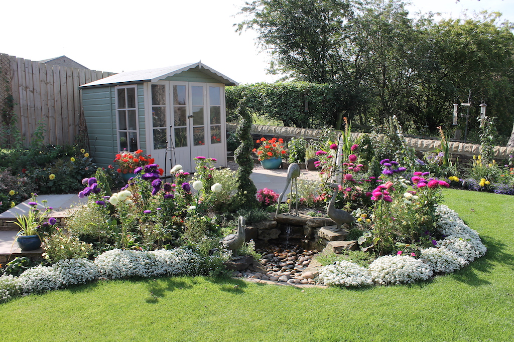 garden with floral centre piece, along with a garden shed and statues