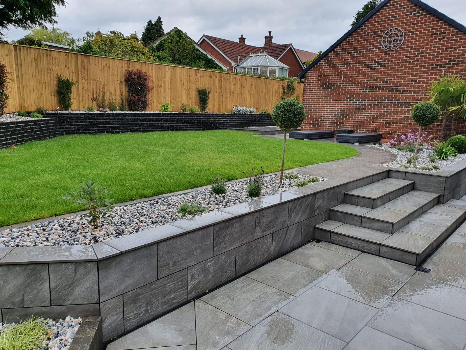 Raised grass garden with grey porcelain patios