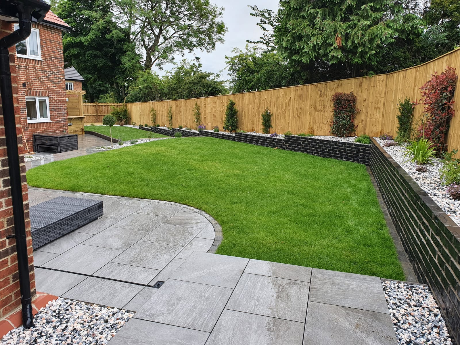 Corner of a garden with grey paving and curved grass