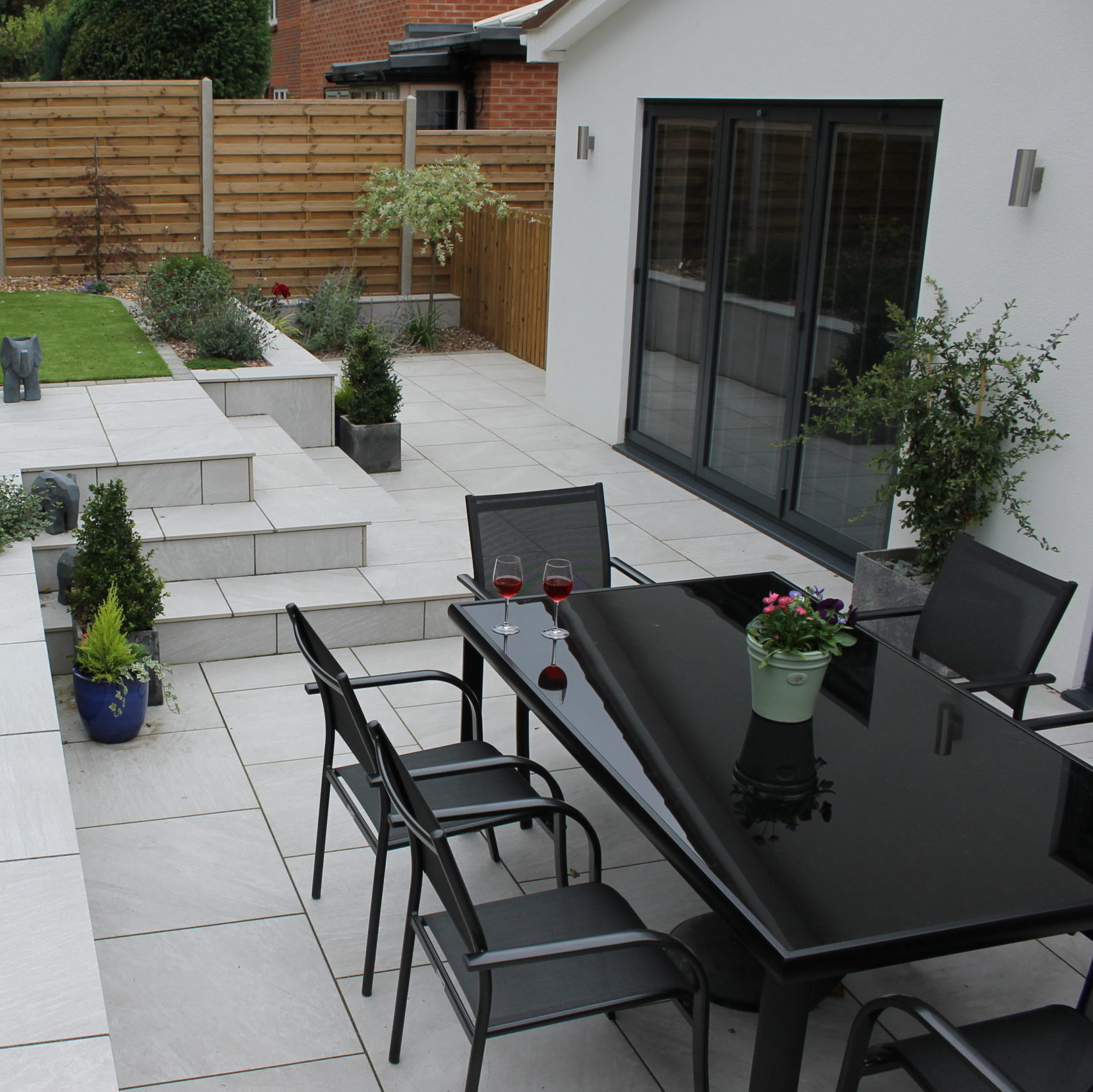 White Patio with black garden furniture and raised grass