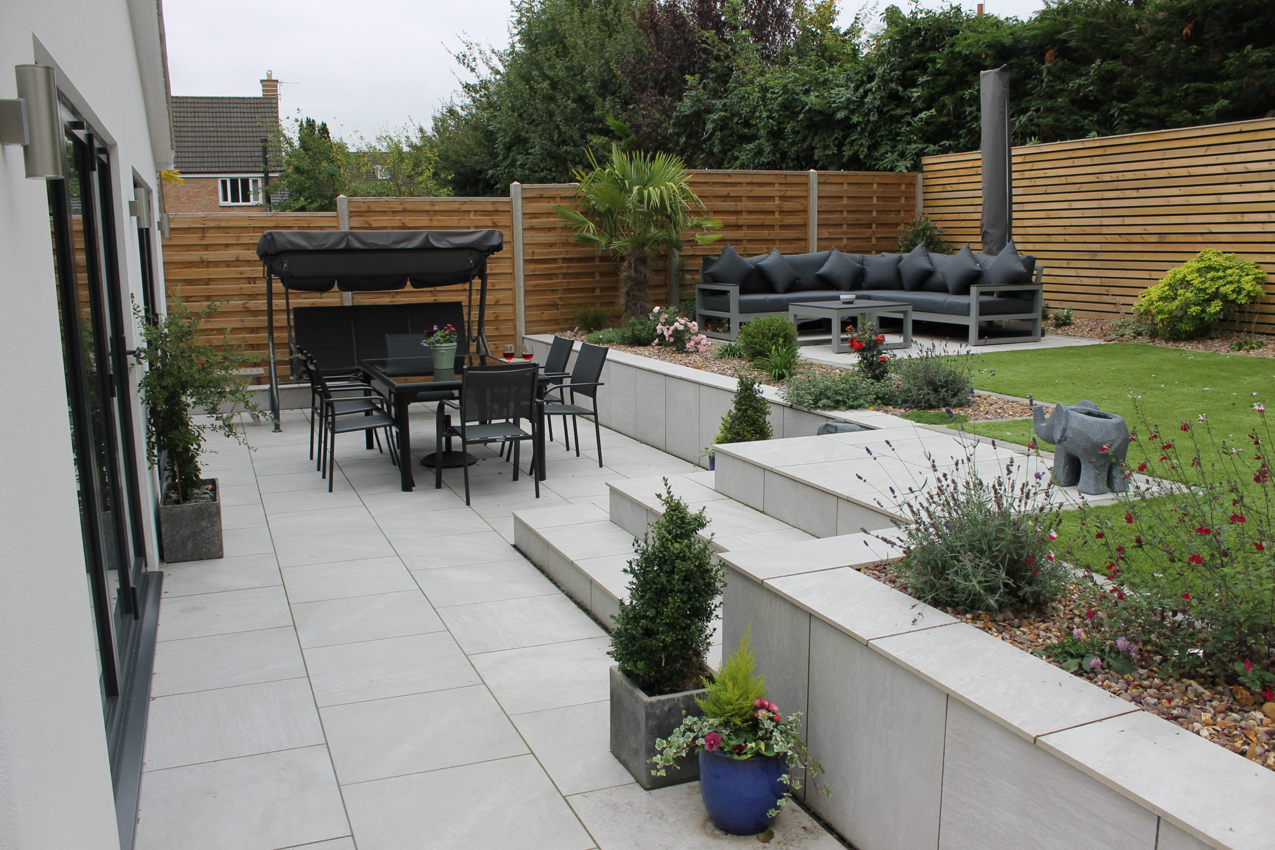 Porcelain paved garden with black table chairs and couch