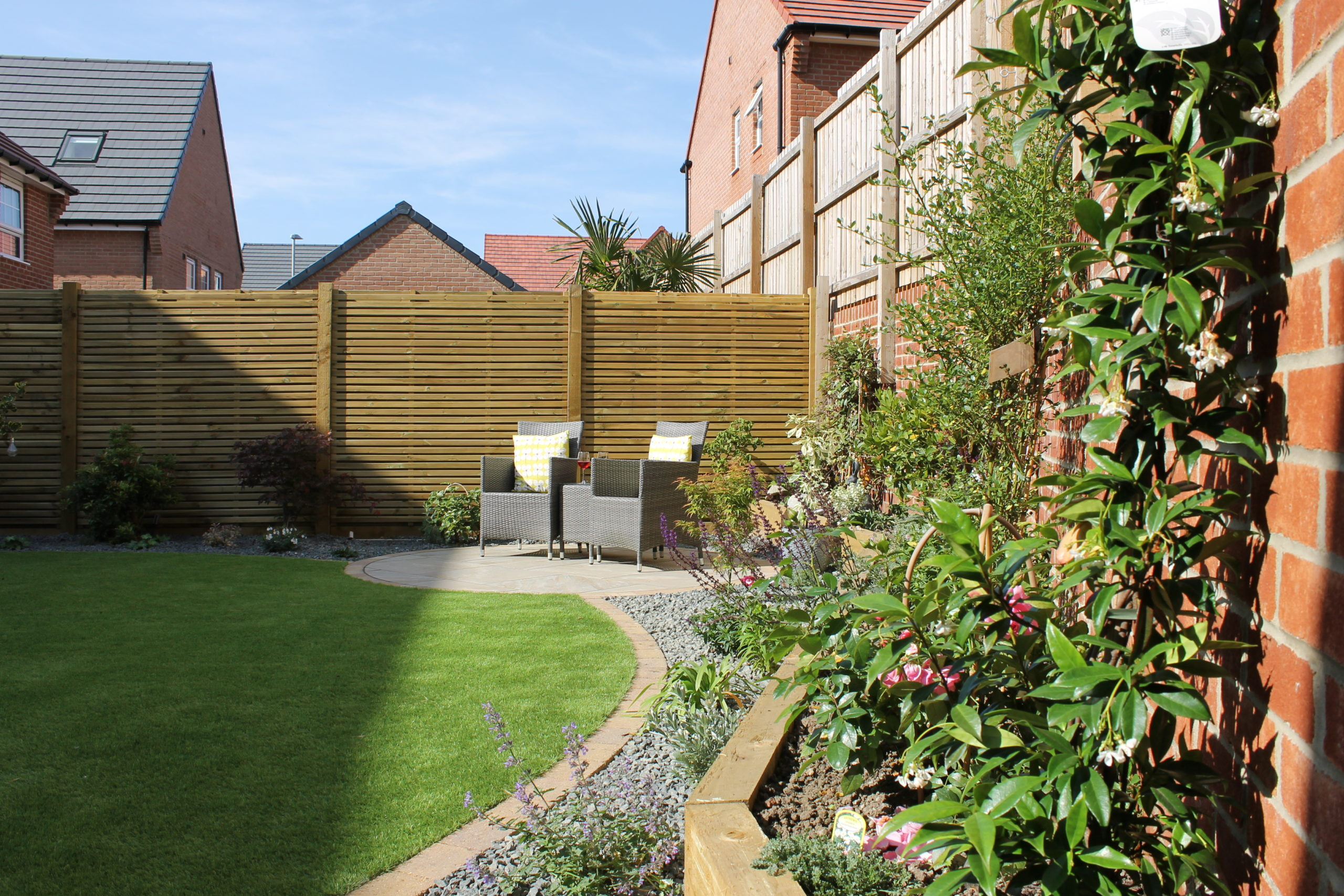 Corner of a garden with a brown fence, plants and grey chairs